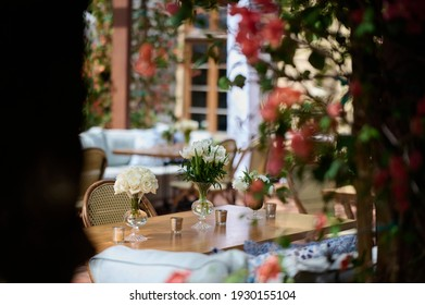 Table setting with vases with white flowers and candles on the background