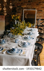 Table setting with vintage porcelain tableware, mimosa flowers and candles.