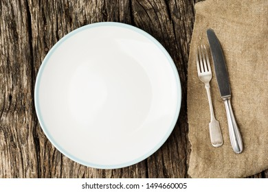 Table setting with vintage silverware or cutlery and empty plate on rustic wood. Top view.