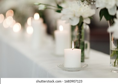 Table setting at wedding reception. Floral compositions with beautiful flowers and greenery, candles on decorated table. Coziness and style. Modern event design. selective focus.