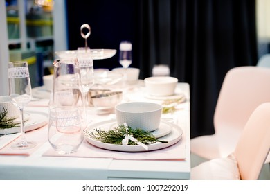 Table setting in white color, with decoration of green. Table setting for event party or wedding.  Decor in green and white colors.Catering in restaurant.