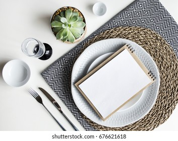Table setting. White dishware, monochrome napkins, Cutlery, glass and plants. The view from the top.