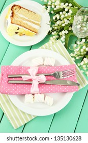 Table setting in white and pink tones on color  wooden background