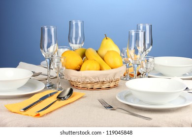 Table setting in white and yellow tones on color  background