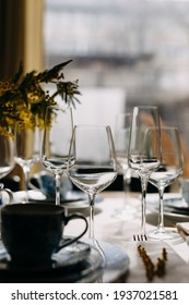 Table setting with wine and champagne glasses in daylight.