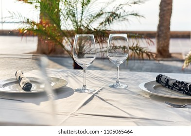 Table setting with a wine glasses, cutlery and plates. Outdoors restaurant. Tropical landscape