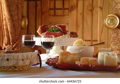 Table settings for a special occasion. Cheese assortment, bread and red wine in a glamorously styled room