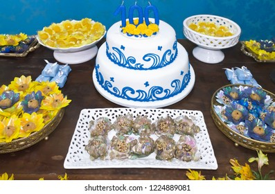 Table with several decorated candy trays and birthday cake - celebrating 100 years