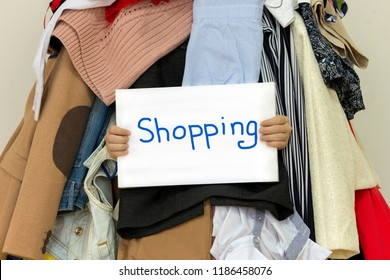"""Table """"Shopping"""" is shown from inside of a big pile of different clothes"""