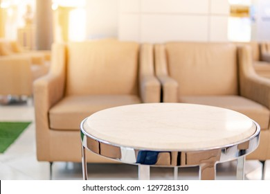 Table and sofa in waiting area of luxury hospital or hotel. Clinic interior background. Healthcare and medical concept. Focus on circle table.
