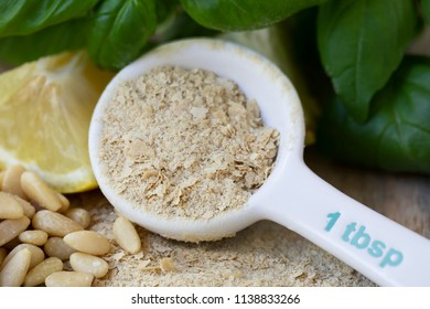 Table spoon of nutritional yeast for making vegan pesto.