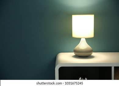 Table with stylish lamp near color wall
