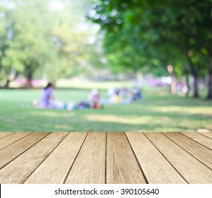 Table and summer park background, Blur family picnic at outside green tree garden background, Empty perspective wood table top over blur people at nature park in spring, summer backdrop, banner