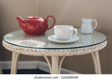 A table with a teapot and two glasses