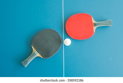 Table tennis bats and ball on a table with white vertical line. Concept of competition
