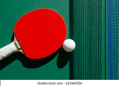 Table tennis bats and ball on a green table .