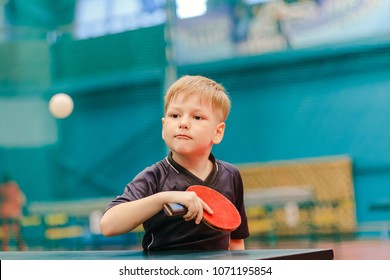 table tennis game, concentrated boy plays tennis ball in the tennis hall