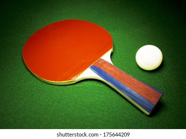 Table Tennis paddle and ball resting on green felt, nice concept of activity or competition