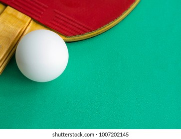 Table tennis racket with a ball on green background. Ping-pong. Image with copy space, selective focus.
