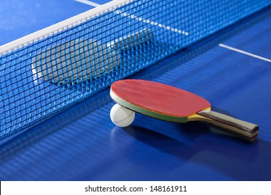 Table tennis rackets. Top view of table tennis racket lying on the tennis table on the both sides of net