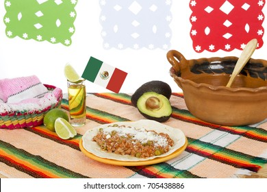 Table with tequila shot and national meal in composition of clay pottery and fresh fruit.
