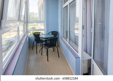 A table and three chairs on the balcony in the apartment of a multistory apartment building