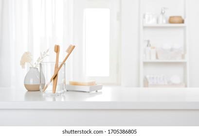 Tisch mit Zahnbürsten und Seife in einem hellen, dezenten Badezimmer