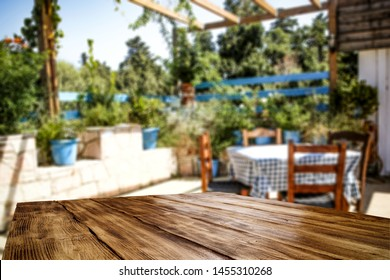 Table top background and blurred sunny garden forest view in distance. Empty space on the table top for an advertising product.