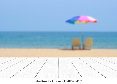Table top and beach sand for vacation product display background, Perspective white wood table, shelf, counter over blur blue sea beach with sand and sky in summer vacation, Backdrop for product