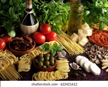 TABLE TOP FILLED WITH ASSORTED FRESH ITALIAN INGREDIENTS: BASIL,HERBS,TOMATOES,PARMESAN CHEESE,SLICED MOZZARELLA,DRIED MUSHROOMS,GREEN OLIVES,ASSORTED DRIED PASTA,SUNDRIED TOMATOES,OLIVE OIL