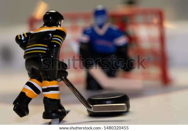 Table top hockey player coming in for a break away shot on the goalie