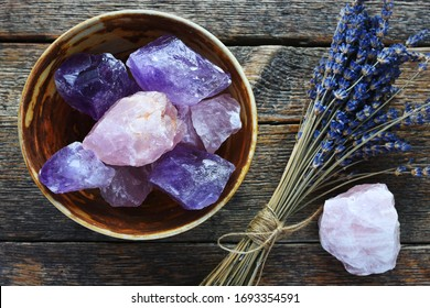 A table top image of a pottery bowl with large rose quartz and amethyst crystal with dried lavender flowers.