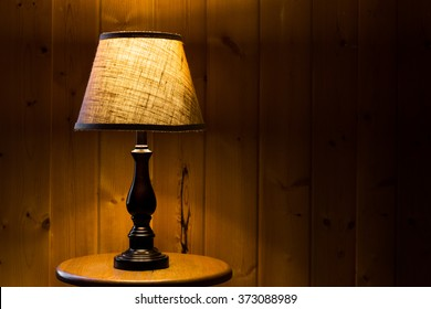 Table top lamp with burlap shade lit over a wooden textured background on a wooden table