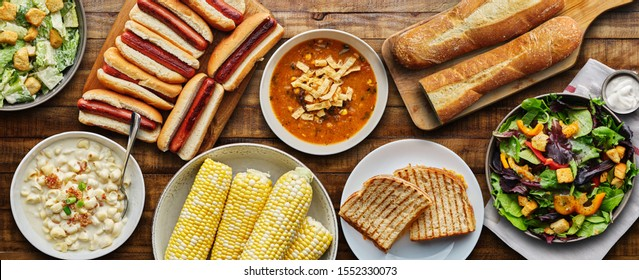 table top meal with hot dogs, grilled cheese, soup and salad in flat lay composition