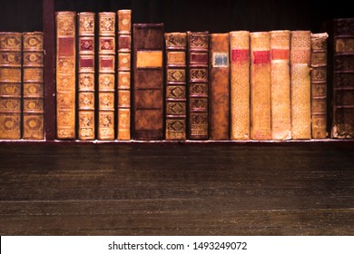 Table top from old brown boards on the background of shelves with old books