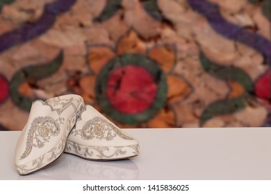 26165ba82 Table top on woman slippers background. Closeup of elegant luxurious  handmade beige ladies slippers with