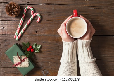 Table top shot of female hands holding a cup of hot coffee next to some Christmas presents and decorations