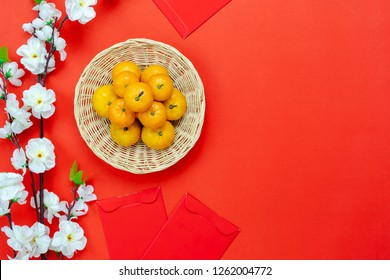 Table top view of accessories on Lunar New Year & Chinese New Year vacation concept background.Fresh orange in wood basket with white flower on modern rustic red backdrop at home office desk studio.