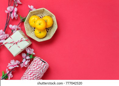 Table top view of accessories on Lunar New Year & Chinese New Year vacation concept background.Orange and gift box with essential accessory on modern rustic red backdrop at home office desk studio.