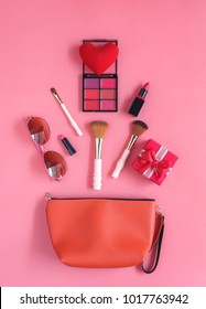 Table top view accessory of clothing women plan to travel in holiday background.Beauty & Fashion concept.Flat lay of hand bag with many essential items cosmetic and sun glasses on modern pink paper.
