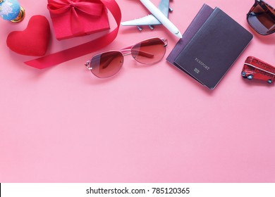 Table top view accessory of clothing women & men to plan travel in valentine's day background concept.Passport & clothes with many essential  items in holiday season.Several objects on pink paper.