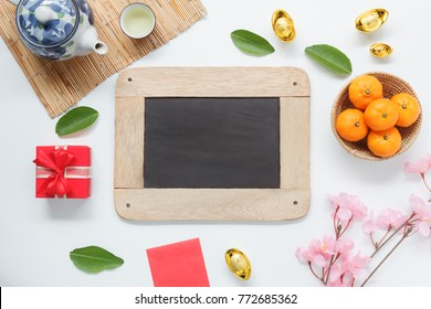 Table top view aerial of accessories on Lunar New Year & Chinese New Year holiday background concept.Blackboard for creative design.Decoration object on modern design white wooden at home office desk.