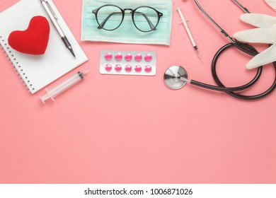 Table top view aerial image of accessories healthcare & medical background concept.Red heart & stethoscope with copyspace on pink paper.Flat lay of idea for doctor treat patient in hospital.