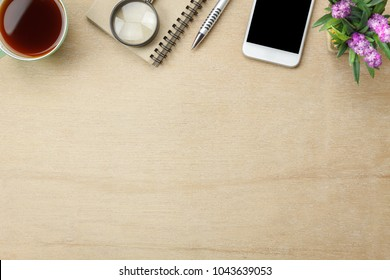 Table top view aerial image stationary on office desk background concept.Flat lay objects the cup of black coffee with essential accessory & tree plant.Items on modern brown wooden at home studio.
