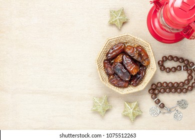 Table top view aerial image of decoration Ramadan Kareem holiday background.Flat lay date in wood basket with brown rosary & red lantern.Essential object star on rustic white wood at office desk.