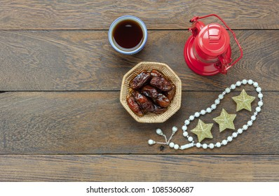Table top view aerial image of decoration Ramadan Kareem holiday background.Flat lay date in wood basket with rosary & vintage lantern.Essential object star on modern rustic wooden at office desk.
