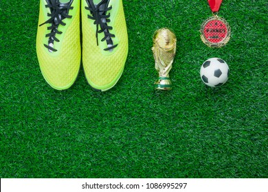 Table top view aerial image soccer or football season background.Flat lay accessories trophy & ball with shoe and medal on the artificial green grass wallpaper.Free space for design text and content.