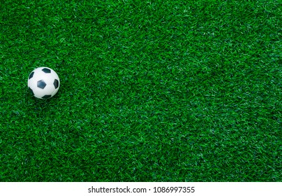 Table top view aerial image soccer or football tournament season background.Flat lay object on the artificial green grass wallpaper.Free space for design mock up text and content.