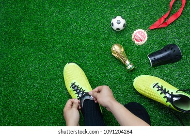 Table top view aerial image soccer or football tournament season background.Flat lay player wear shoe with gold medal & ball on the artificial green grass wallpaper.Copy space for creative design.