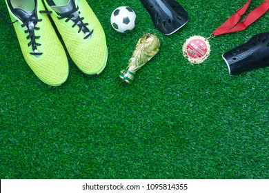 Table top view aerial image soccer or football tournament season background.Flat lay prepare objects for competitive match the shoe with gold medal & ball on the artificial green grass wallpaper.